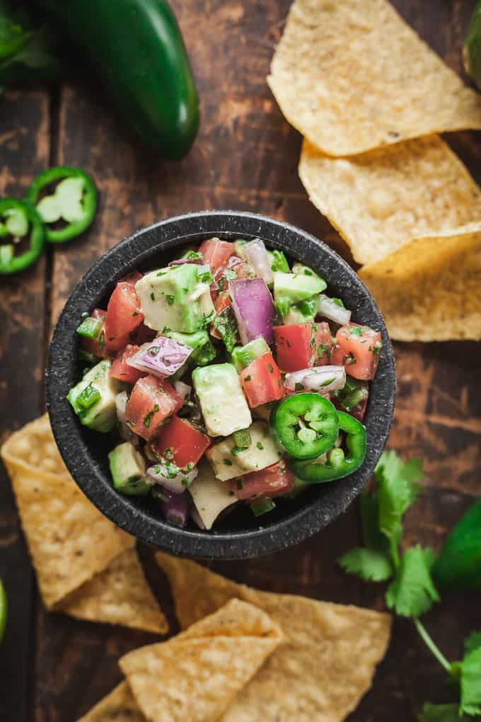 a black bowl of pico de gallo with avocado surrounded by tortilla chips and jalapeno