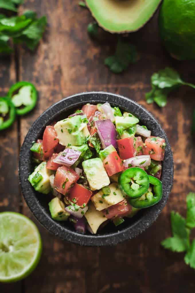 a black bowl of pico de gallo with avocado surrounded by lime, cilantro, jalapeno, and avocado