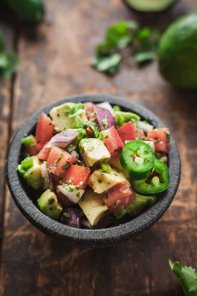 a black bowl of pico de gallo with avocado