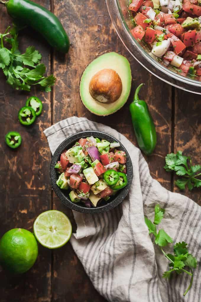 a wood table with a black bowl of pico de gallo with avocado, a striped napkin, avocado, jalapeno, cilantro, and lime