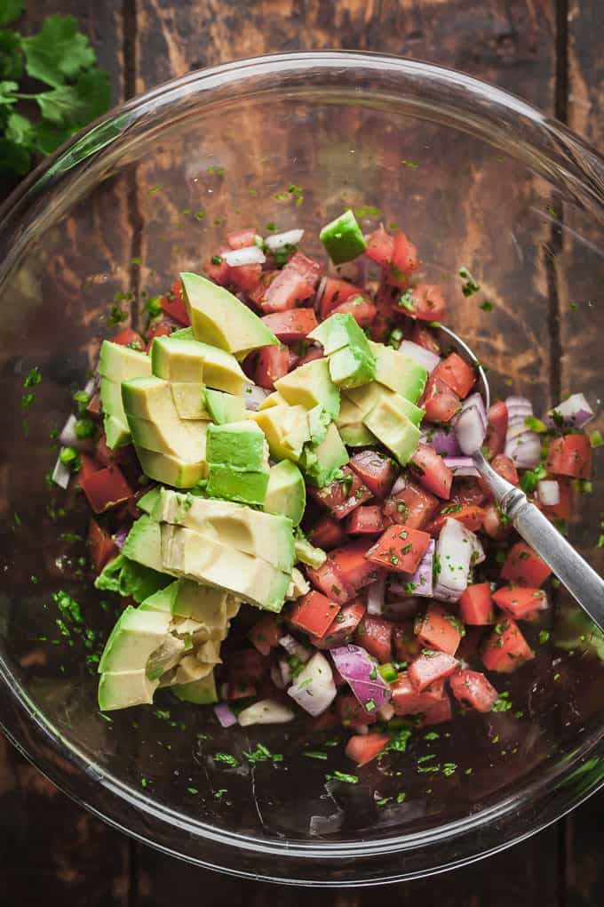 pico de gallo with avocado getting mixed in a clear bowl