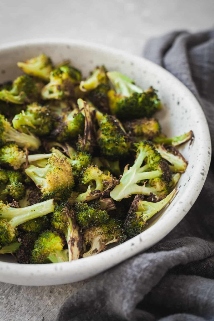 oven roasted broccoli in a white speckled bowl with a grey napkin