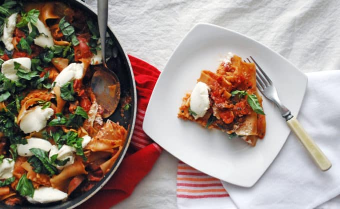 overhead photo of a white plate with a serving of skillet lasagna and more in the pan