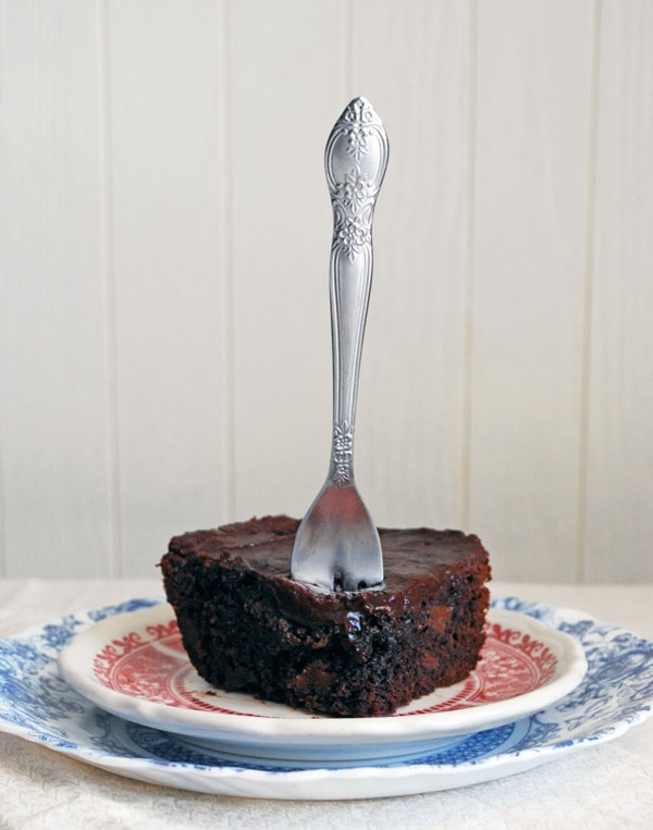 a chocolate brownie on two plates with a fork sticking out of it