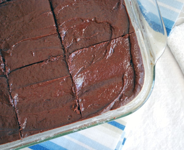 sliced frosted brownies in a pan