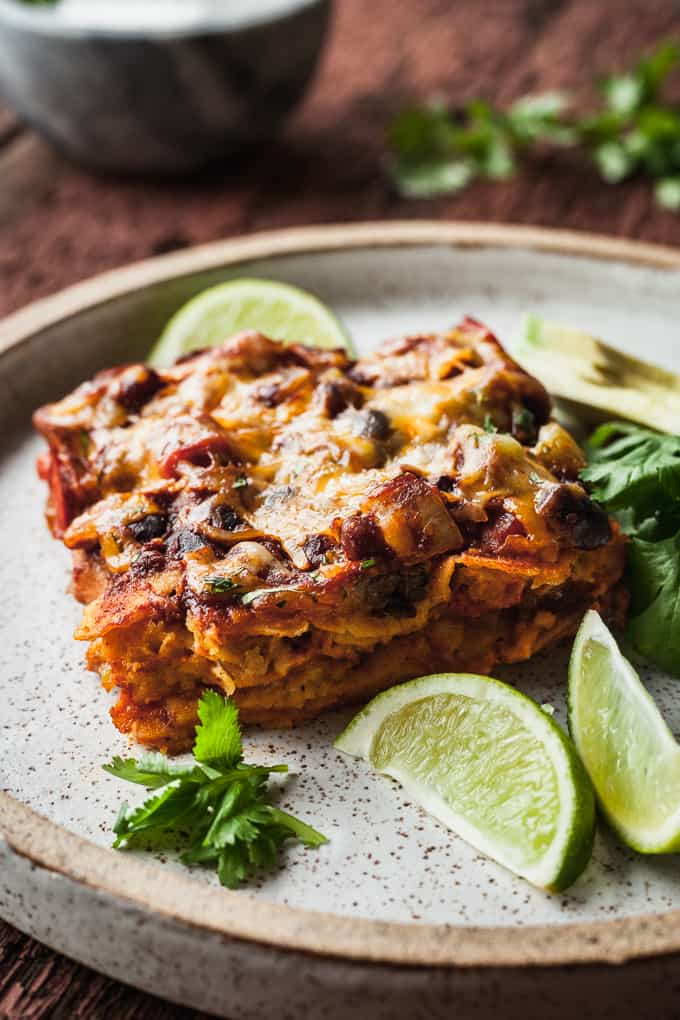 a slice of stacked enchiladas on a rustic plate with cilantro and limes