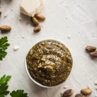 pistachio pesto in a little ramekin with parsley, cheese, and nuts around