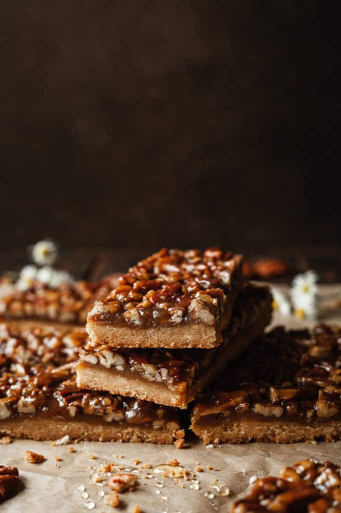 a stack of pecan pie bars against a dark background