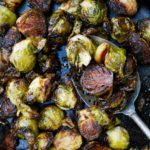 balsamic roasted brussels sprouts with garlic in a cast iron pan with a metal spoon