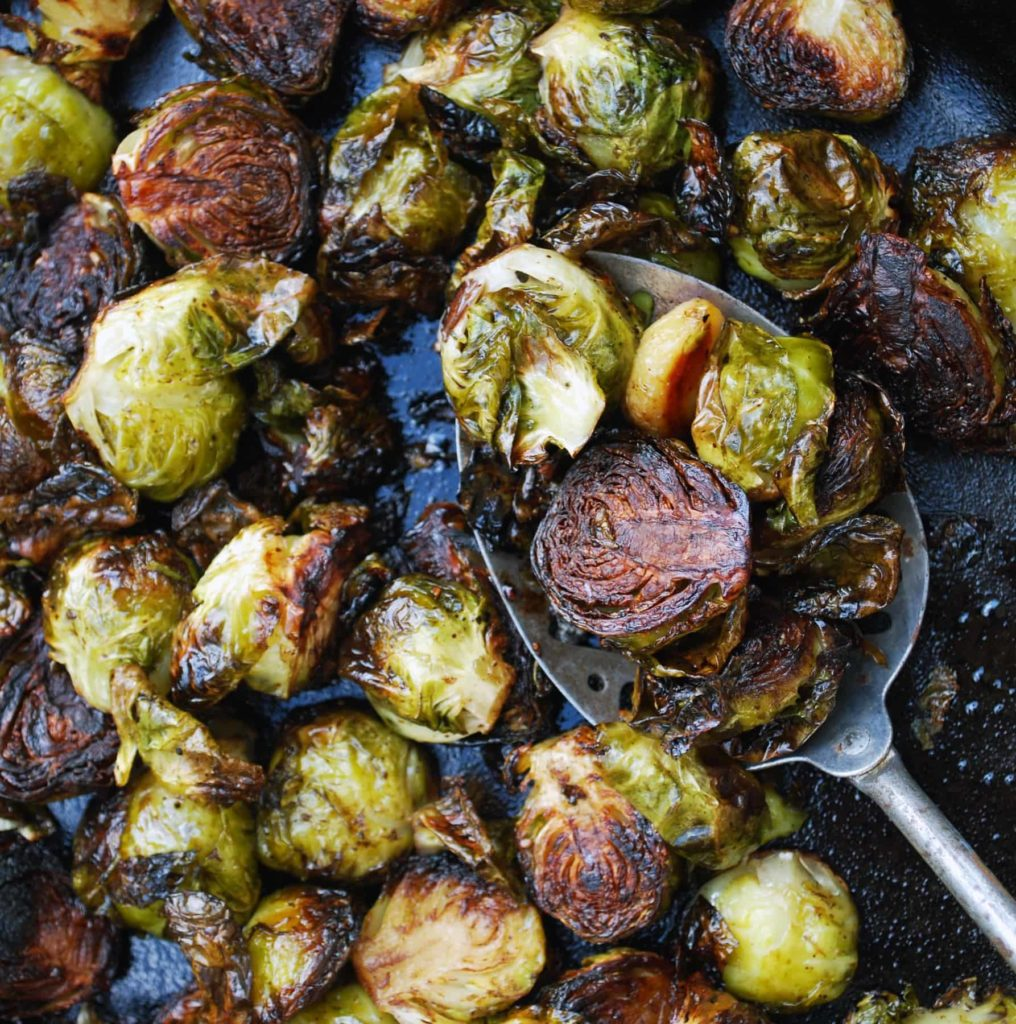 a metal spoon scooping up balsamic roasted brussels sprouts with garlic