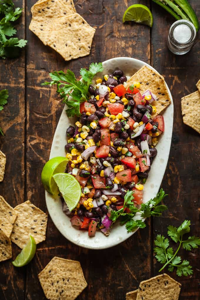 a dish of black bean corn salsa surrounded by chips on a wood table