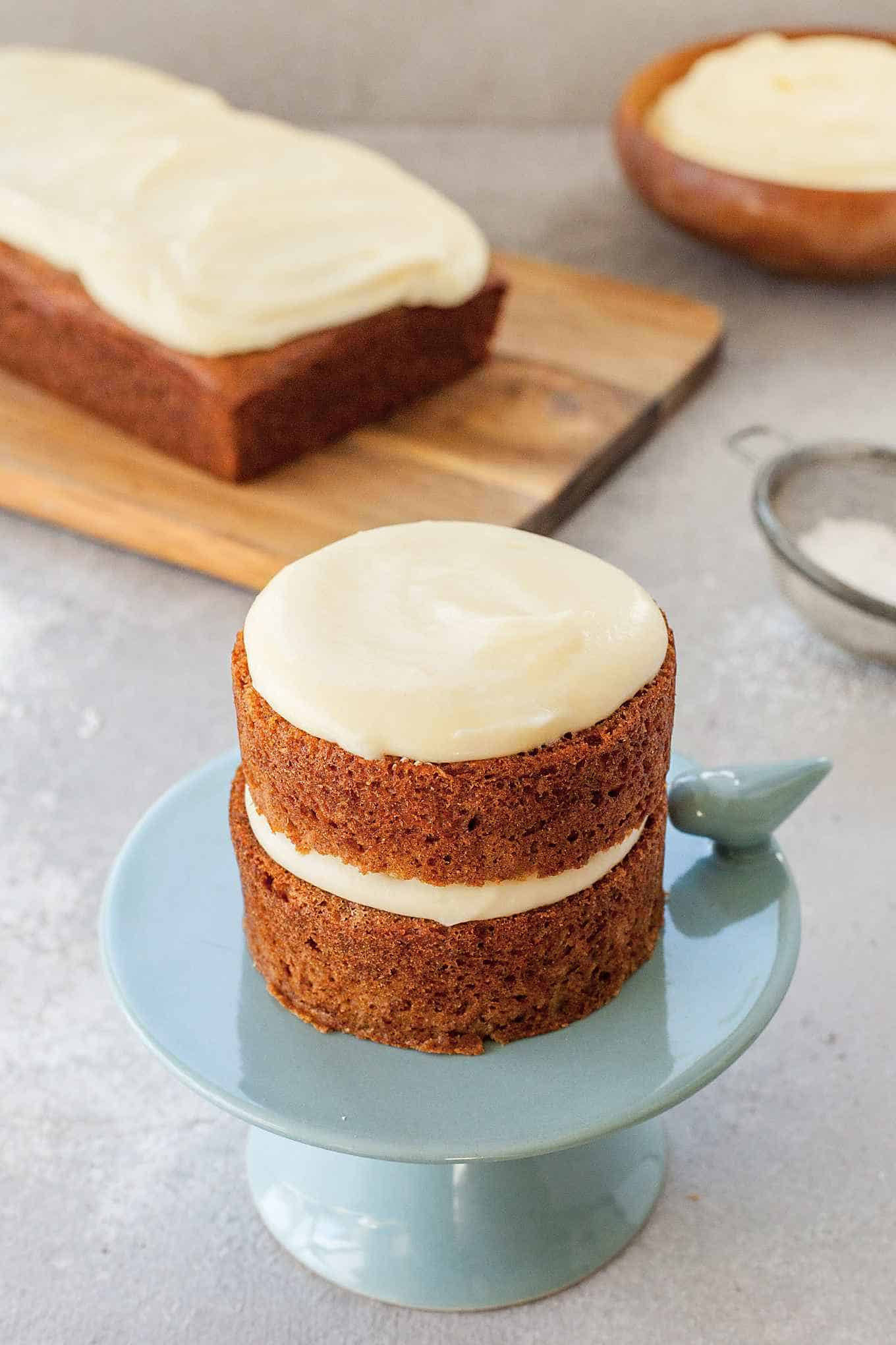 image of applesauce cake on blue cake stand with applesauce cake on wooden board