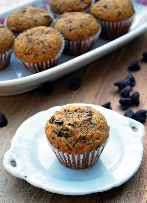 image of mini pumpkin muffins on white tray and one single muffin on white plate