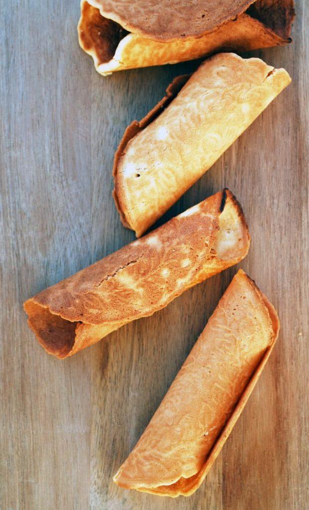 several krumkake on a wood cutting board