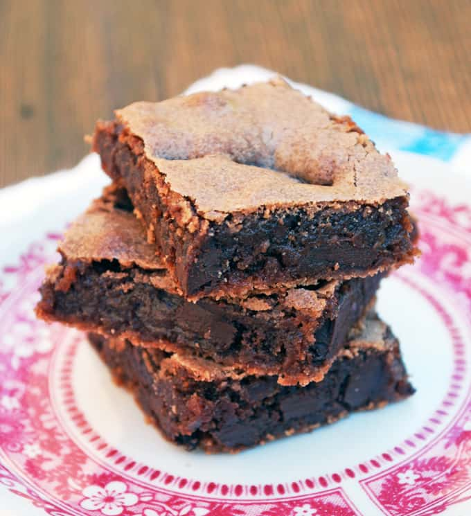 a stack of brownies on a pink and white plate