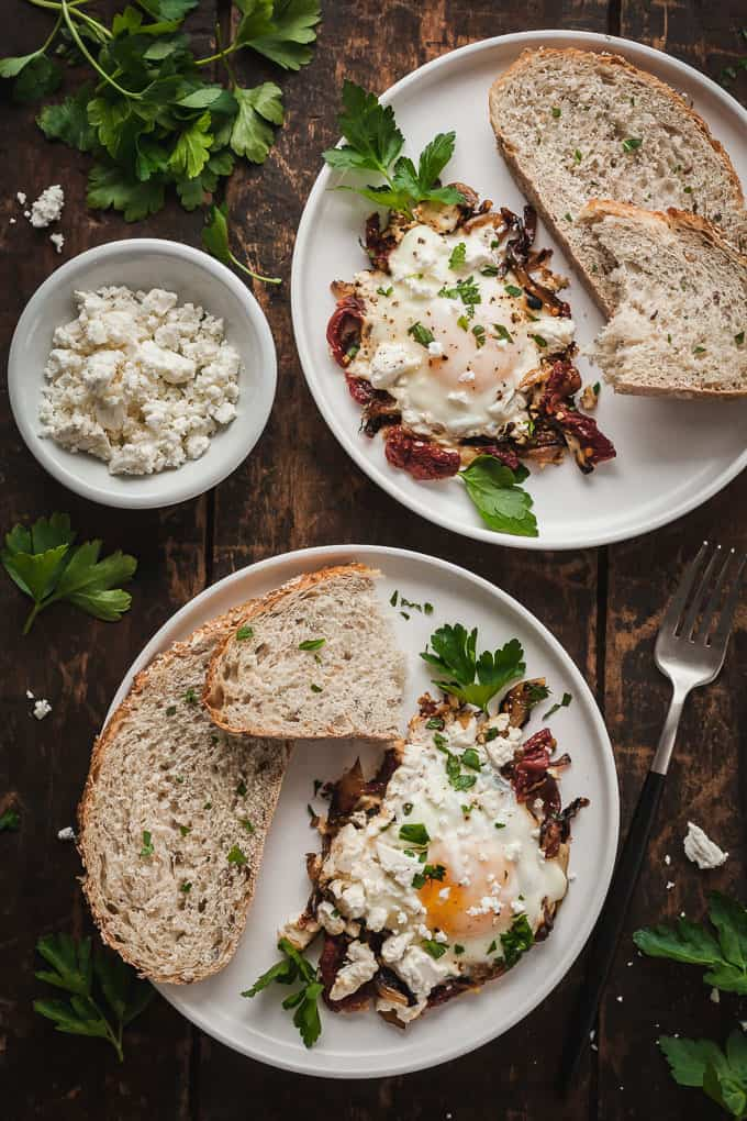 two white plates with mediterranean eggs and bread