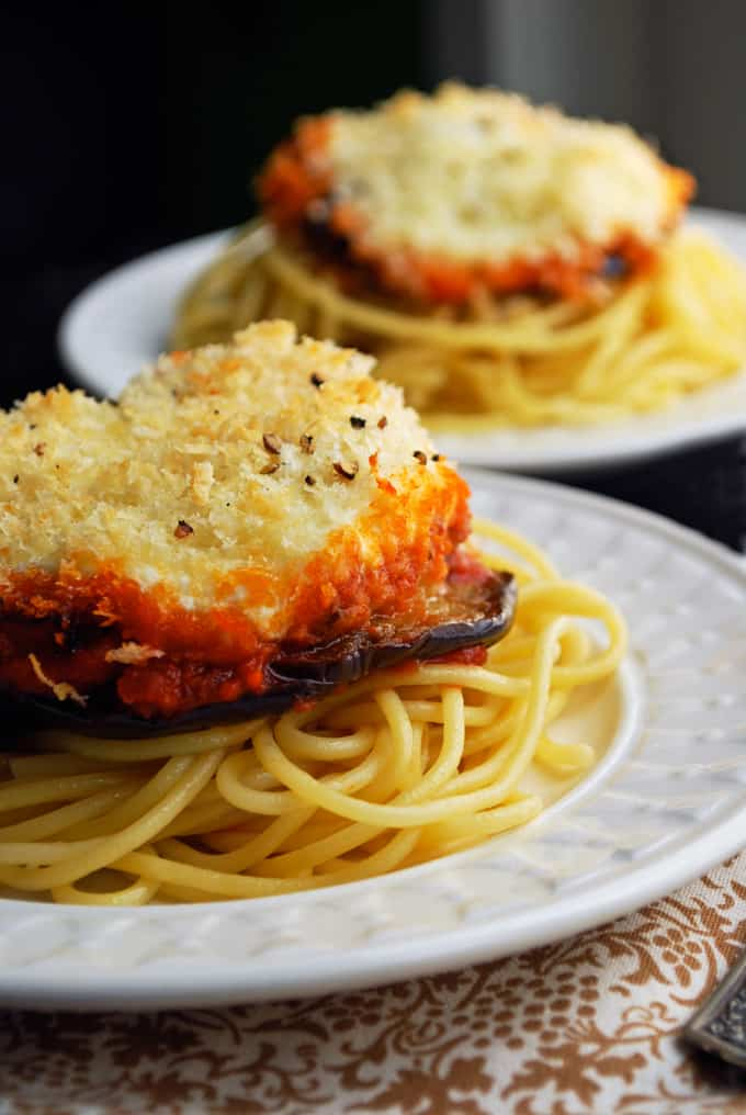 closeup side view of eggplant parmesan on white plate