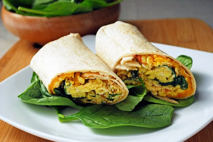 a breakfast burrito on a bed of spinach on a white plate