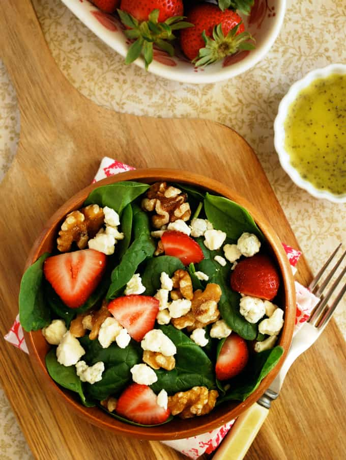 a strawberry spinach salad in a wood bowl