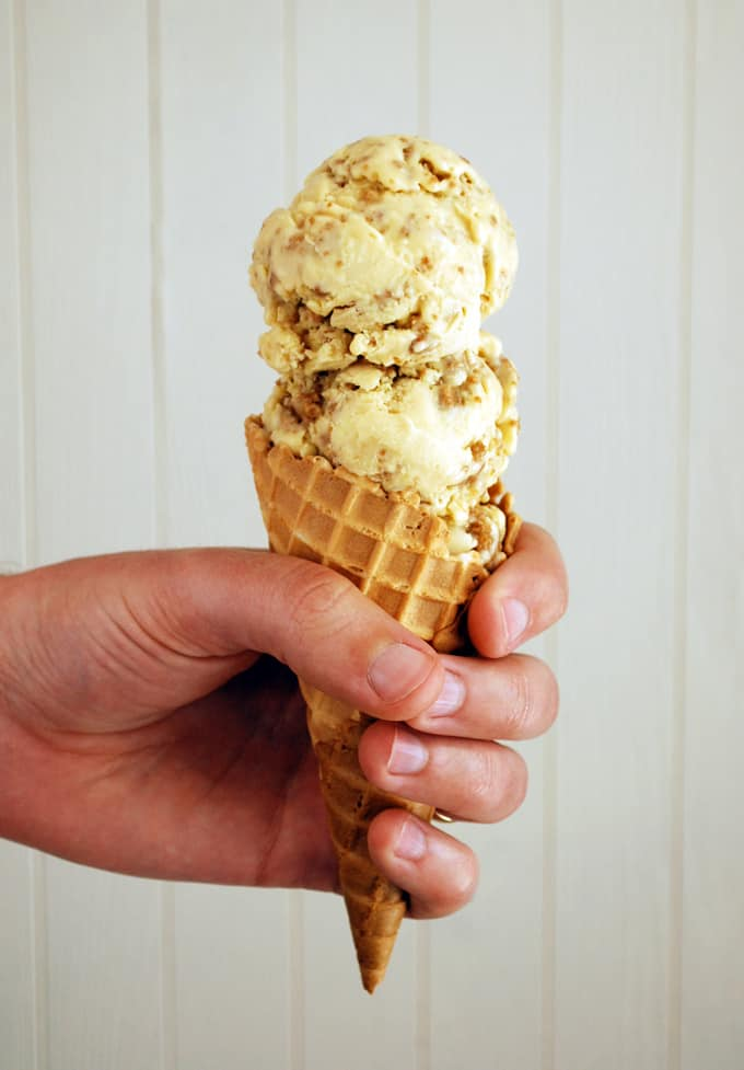 a hand holding a double scoop if grape nut ice cream in a waffle cone