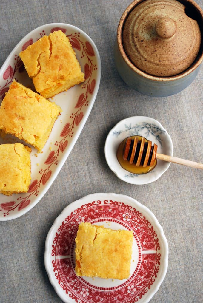 cornbread slices on two plate with honey
