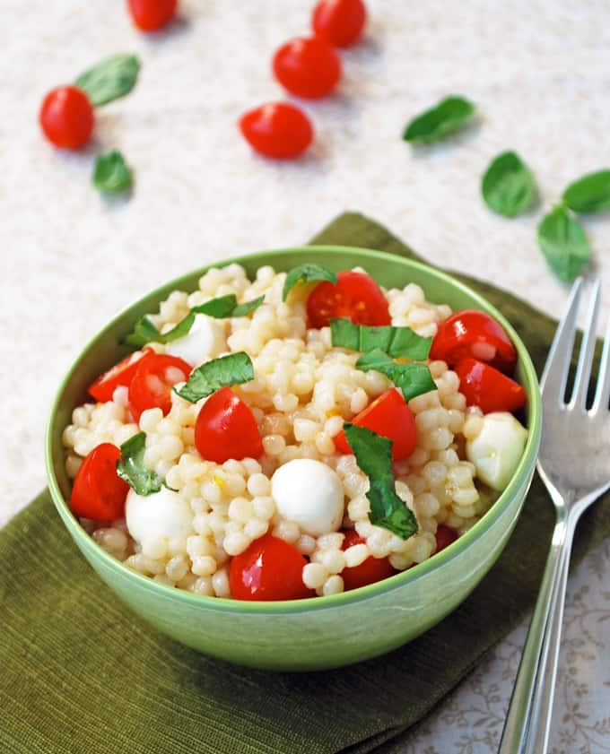a bowl of caprese couscous with a fork and napkin