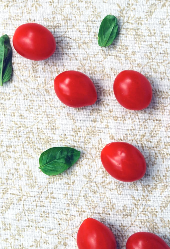 grape tomatoes and basil on a flowery linen