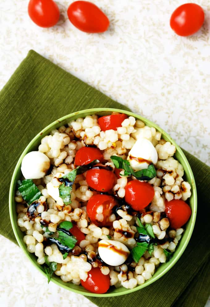 a bowl of caprese couscous salad with balsamic drizzle on a green napkin