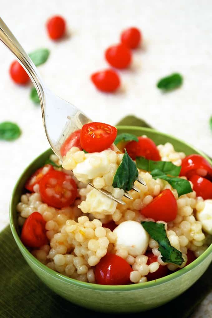 a bowl of couscous with tomatoes, basil, and mozzarella pearls with a fork grabbing a bite