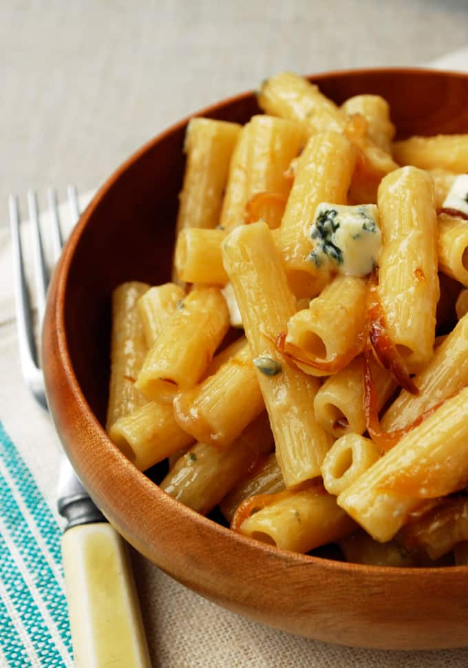 a bowl of rigatoni with caramelized onions and gorgonzola