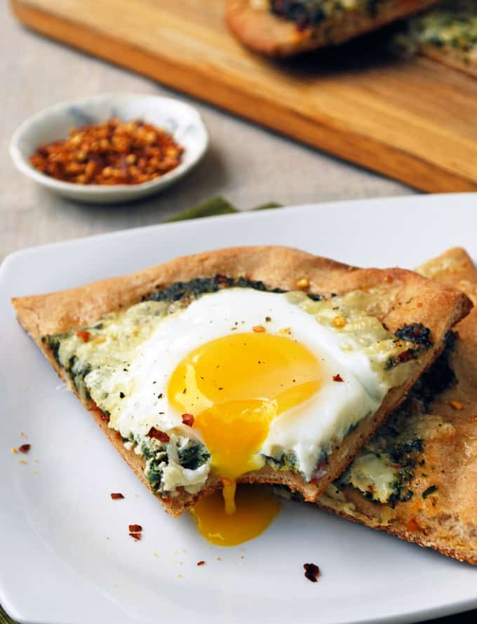 two slices of spinach and egg pizza with a bite taken out and yolk running onto the plate