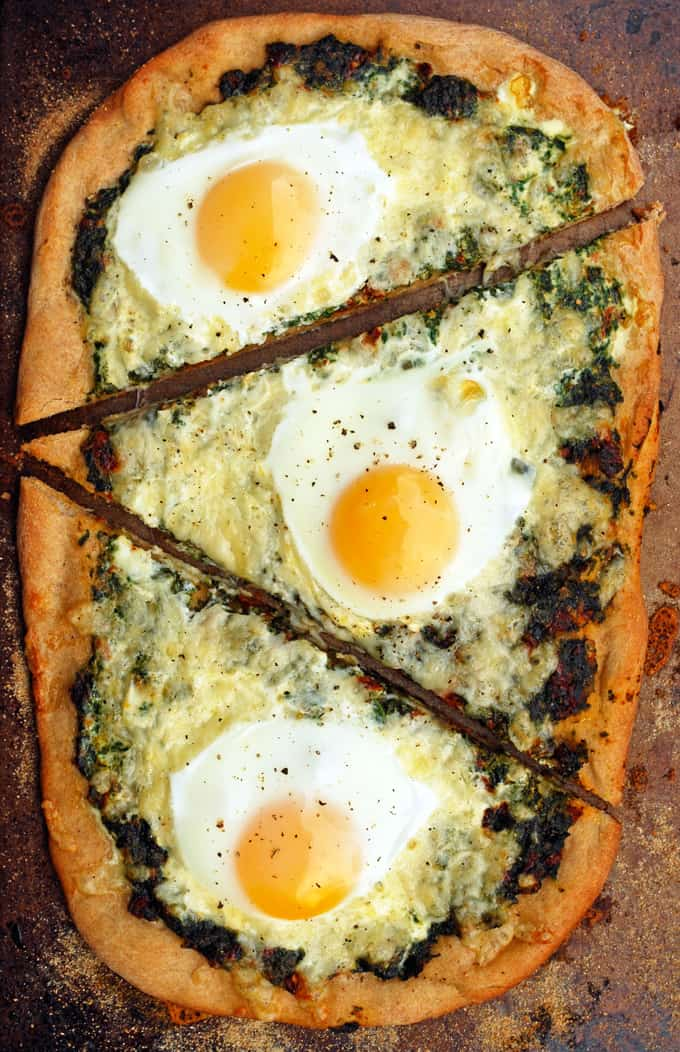 a spinach and egg pizza cut into three slices
