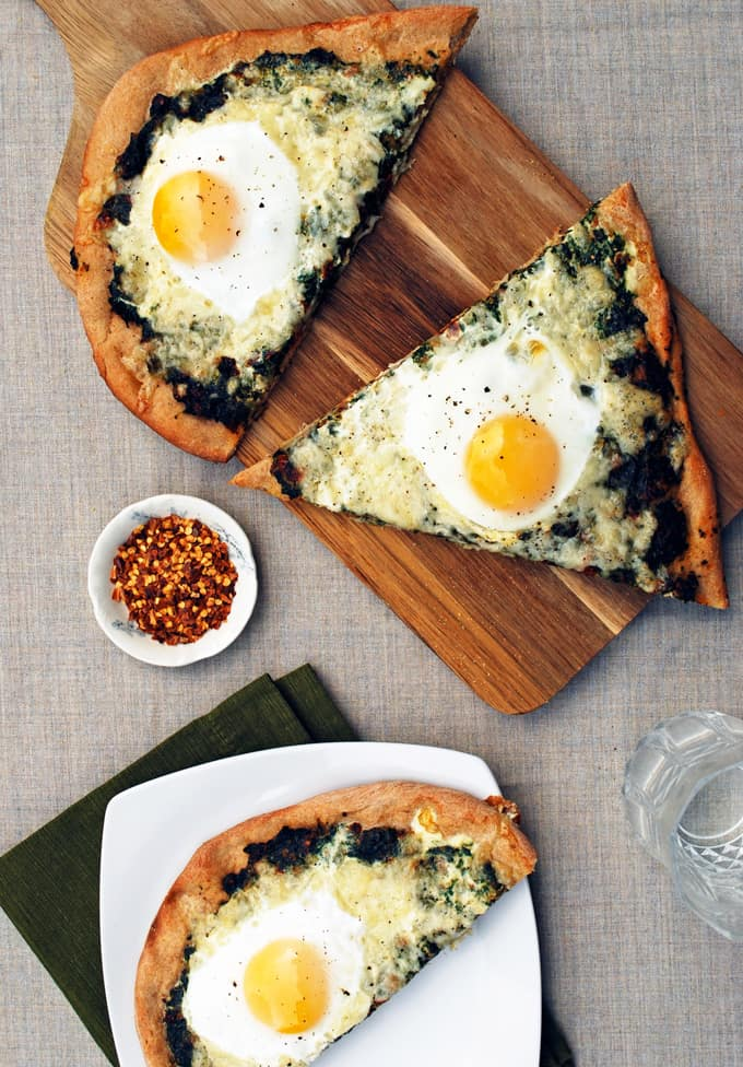 three slices of spinach and egg pizza on a cutting board and plate