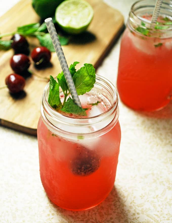 a cherry mojito with mint and a straw