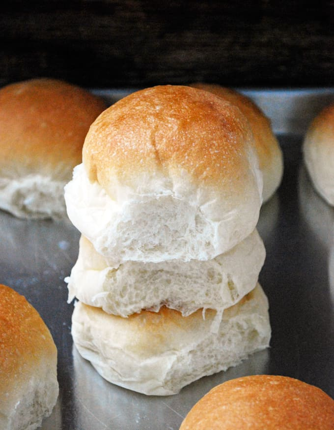 three cranberry dinner rolls stacked on a baking sheet