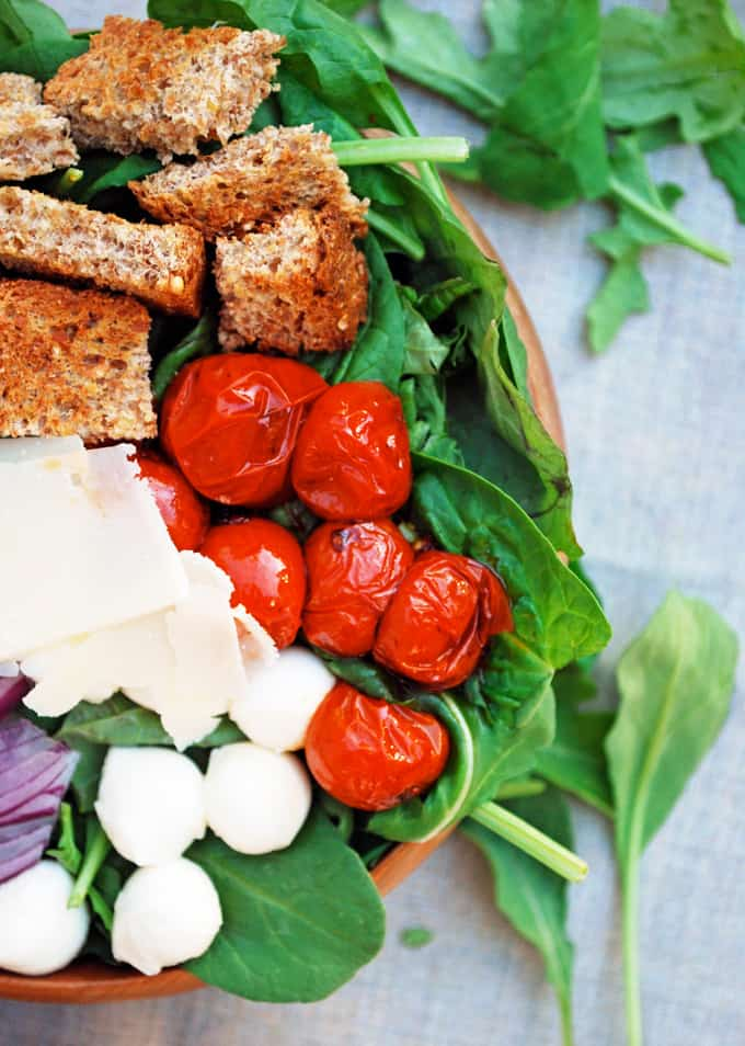 leafy greens, croutons, roasted tomatoes, and cheese in a bowl