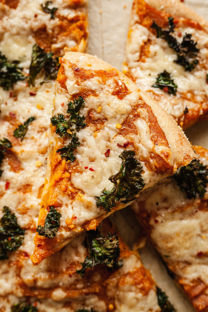 close up photo of a slice of butternut squash kale pizza