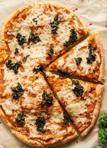 butternut squash pizza with kale on parchment paper