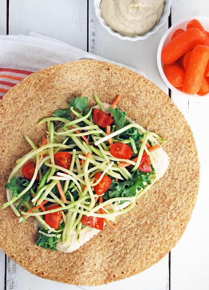 a white bean hummus and veggie wrap open on a plate with a bowl of baby carrots