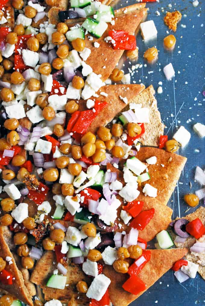 a close up of greek nachos including pita chips, roasted red peppers, onions, olives, and feta