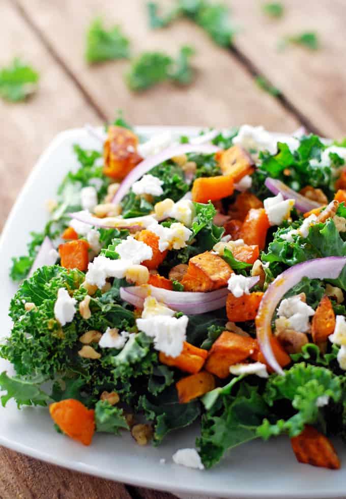 a kale salad on a plate with sweet potato, onions, and feta