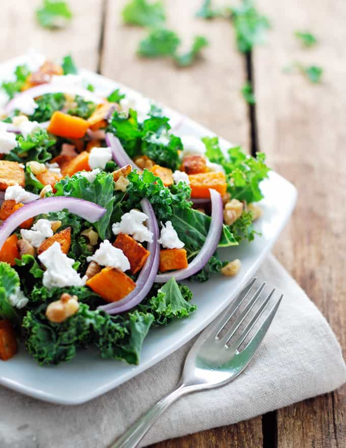 a salad consisting of kale, onion, sweet potato, walnuts, and feta on a white plate on a wood table with a fork and napkin