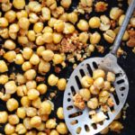 close up of roasted chickpeas in a pan with a slotted spoon