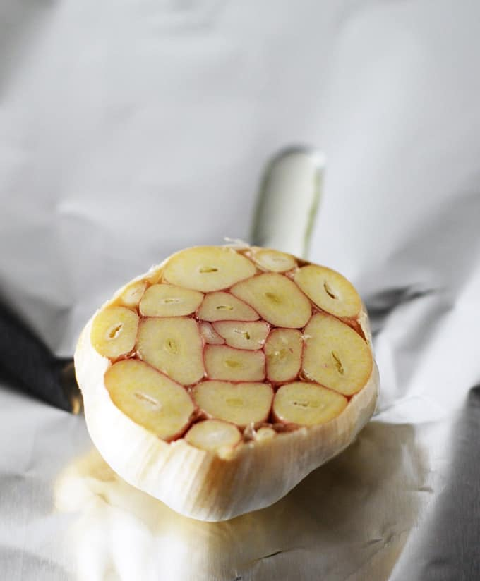 a head of garlic sliced open and covered with oil to be roasted