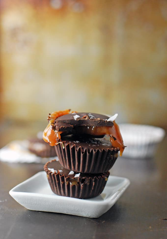 a stack of three dark chocolate salted caramel cups on a tiny white plate, the top caramel cup bitten into and oozing out