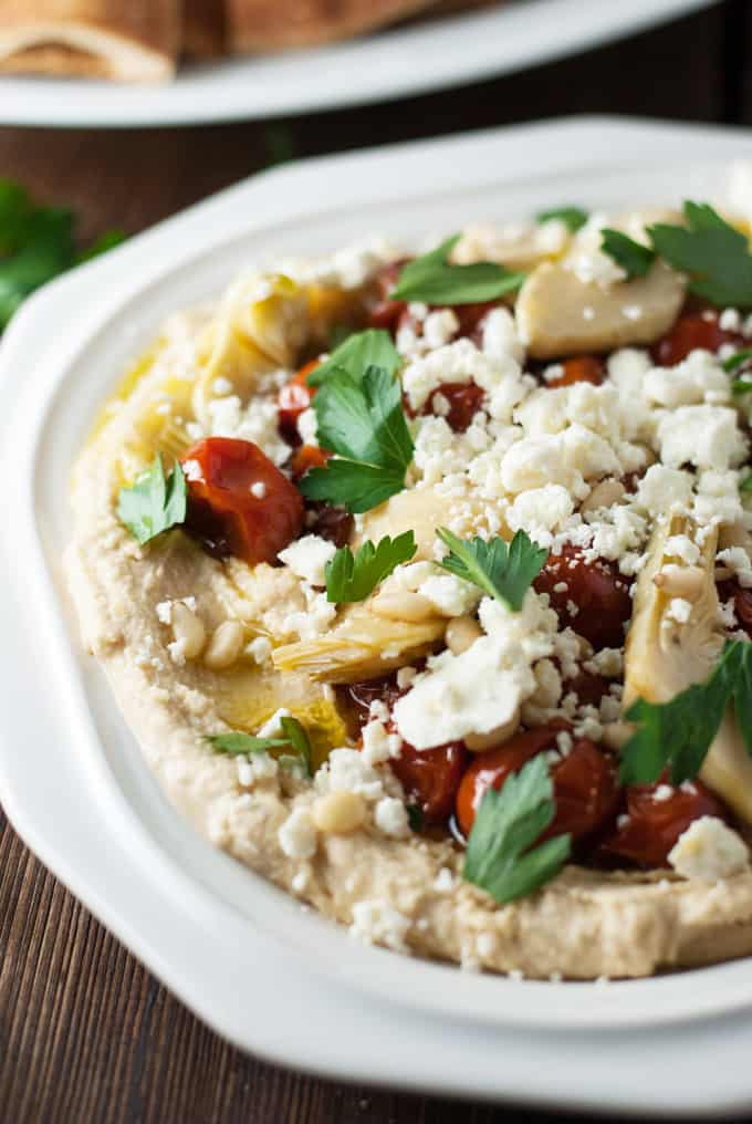 hummus on a white plate loaded with toppings