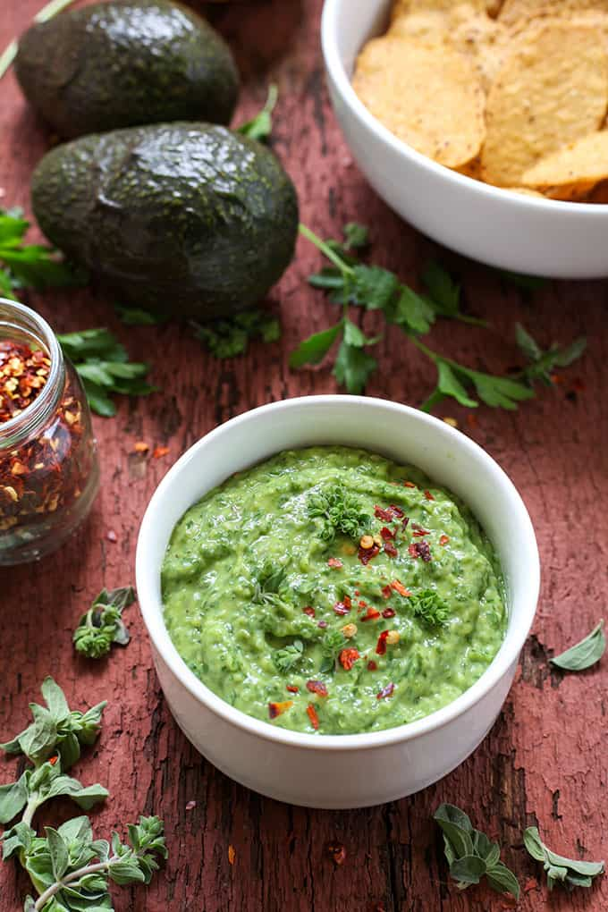 a bowl of avocado chimichurri chip dip with avocados, herbs, and chips