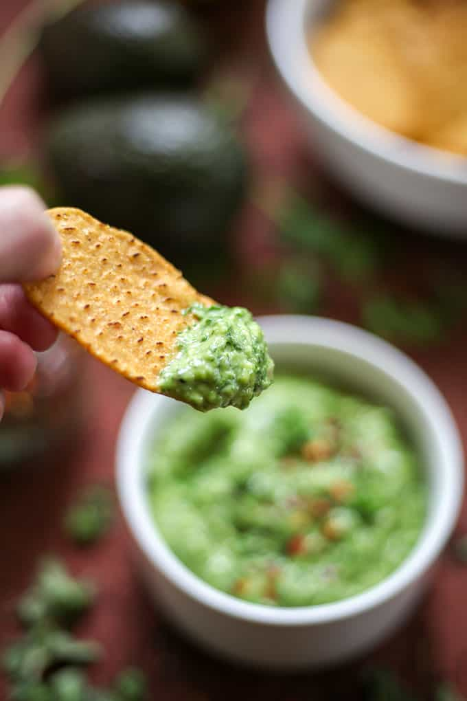 a chip grabbing some avocado chimichurri chip dip