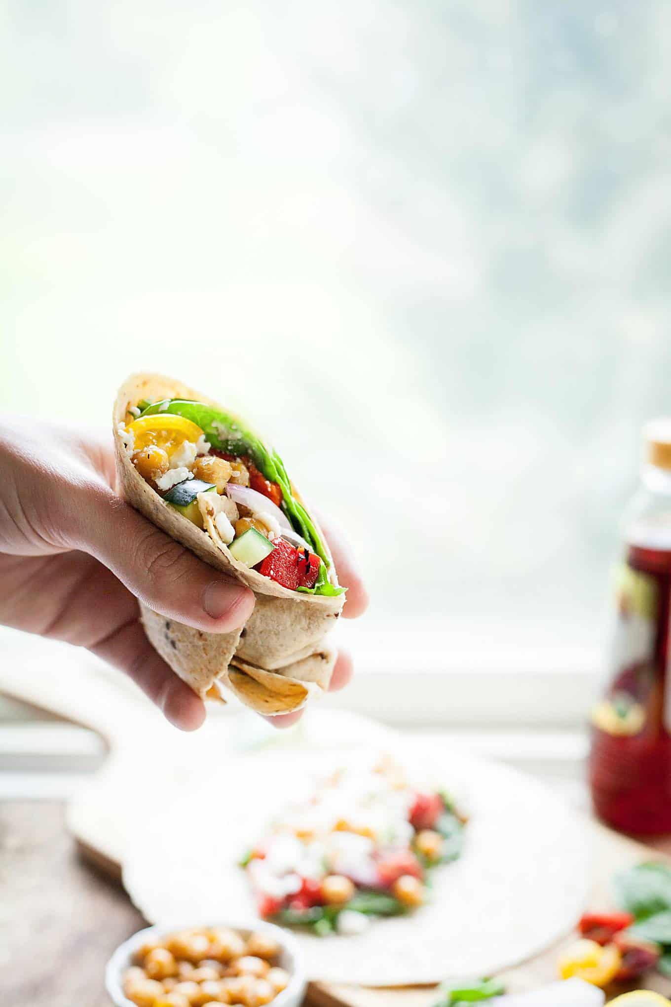 a hand picking up half a greek chickpea sandwich