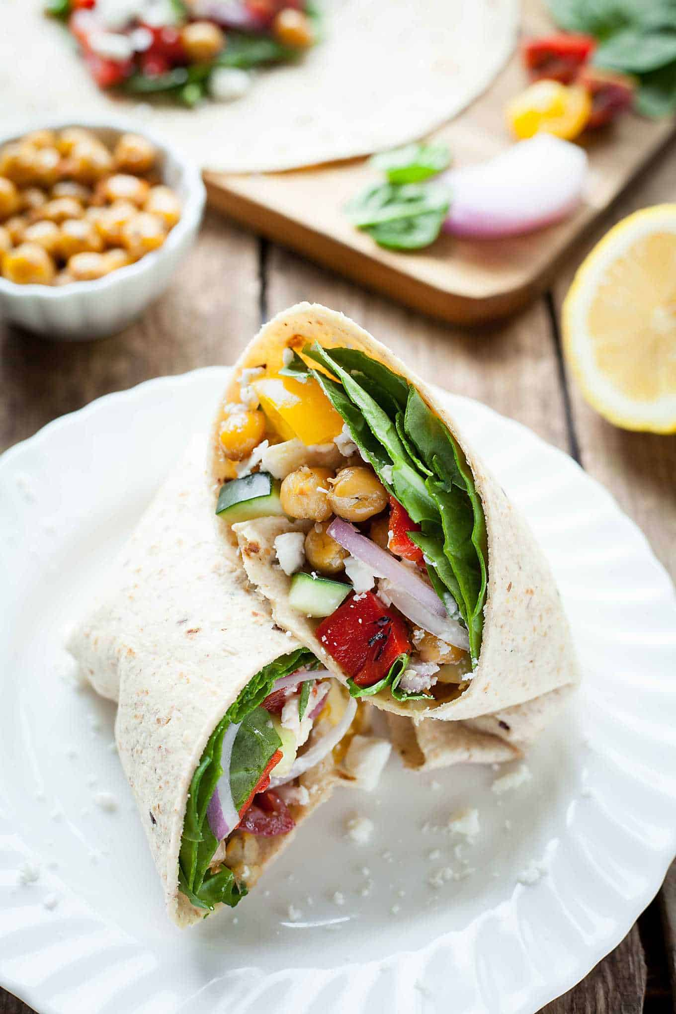 a greek chickpea wrap cut in half on a plate